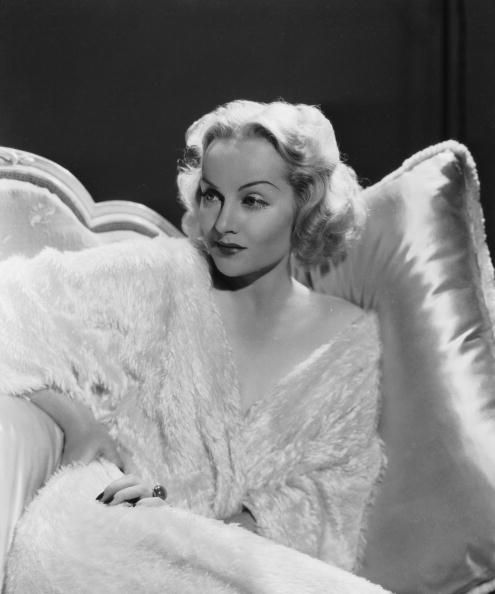 American film actress Carole Lombard reclines on a satin cushion in a textured gown
