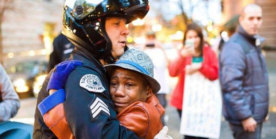 Un bambino nero, il volto rigato dalle lacrime, abbraccia un poliziotto che con elmetto e divisa ricambia con affetto. Il contesto in cui il momento è stato immortalato rende tutto più significato: era il giorno della protesta di Ferguson, in cui le strade dell'America e del Missouri si sono infiammate contro la decisione della giuria di non processare il poliziotto Darren Wilson che uccise Michael Brown.