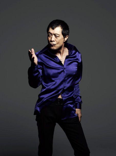 ブルーのサテンのシャツを着て立っている矢沢永吉の画像