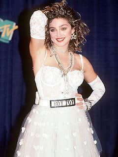 """Madonna in a white wedding dress with controversial """"Boy Toy"""" buckle and fingerless lace gloves at the 1984 MTV Video Music Awards."""