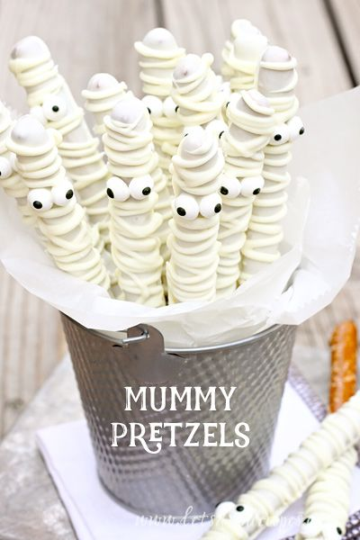 White Chocolate Mummy Pretzels Recipe: Simply coat pretzels in melted white chocolate to make these addicting snacks. Part salty, part sweet, you won't be able to get enough.