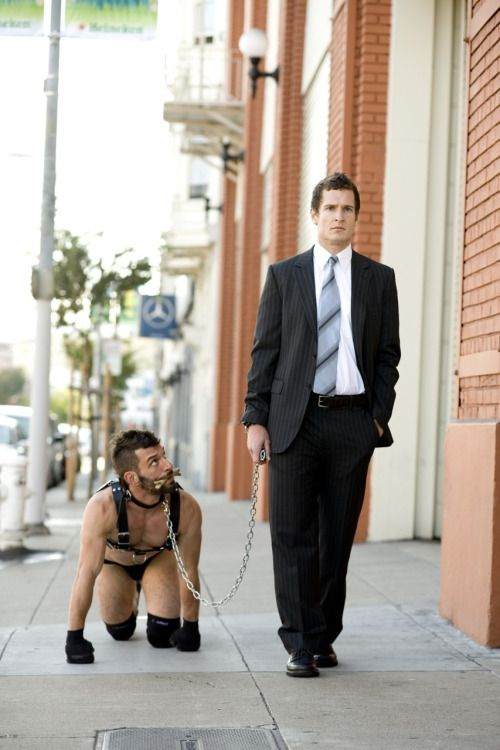 "Walkies!  Normally I'm a true gear pervert, but this image is just too fuckin sexy not to share. The way the suited Handler is just out, walking His dog after a hard day at work - but His pup is all eyes on his Man: looking up at Him with that adorable look of ""were are we going, Sir?""  Nice to see Sir has His pups paws and knees nicely protracted from the hard pavement too. Shows He cares for His dog. No matter what…"
