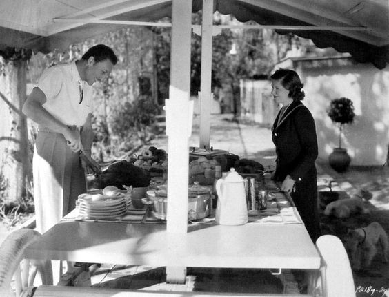 Warren William and his wife Helen set the table for a luncheon in the garden of their Encino ranch. The table was built by William on the chassis of an ancient automobile - 1937