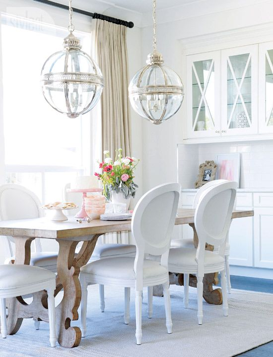 Cheerful white dining room with natural woodo farm table and Louis oval back dining chairs. Beautiful Classically Refined Rooms on Hello Lovely Studio.