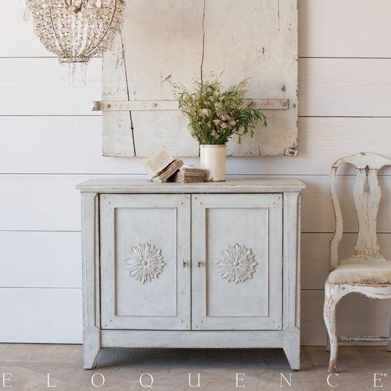 The Eloquence Carenza Cabinet is a re-edition of a French farmhouse antique. The large hand-carved rosettes on each door and small peg details are evocative of simple provincial woodworking style. Adjustable shelves inside the double doors.