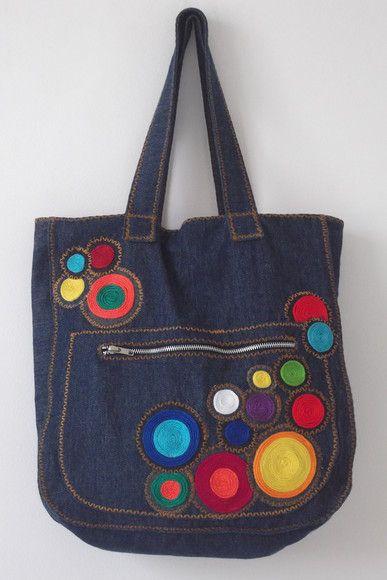 Bolsa jeans bordada com fios de lã. Fecho de zíper, com um bolso frontal