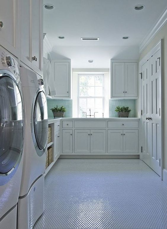 Blue and white Laundry Rooms. Blue and white laundry room features white cabinets paired with white marble countertops and blue glass subway tiled backsplash, White cabinets are suspended over white front-load washer and dryer next to built-in shelving filled with woven baskets atop vintage hex tiled floor. #Blueandwhite #LaundryRooms Brooks and Falotico.