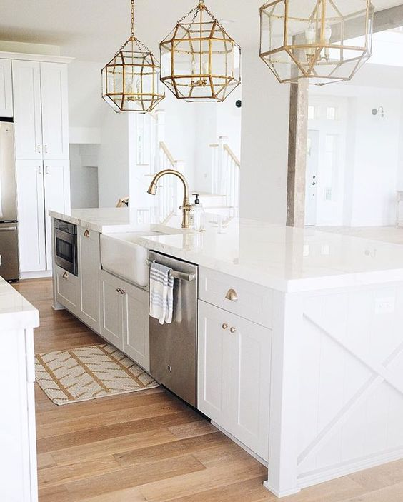 Elegant white kitchen with #brasshardware and gold accents including three glass and brass chandeliers, brass faucet, and brass cabinet pulls.