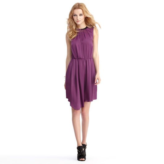 Sleeveless dress with pleated and leather trim details. Asymmetrical hem line.