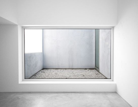 Simple interior, concrete floors, white walls, landscape window looking into small court yard/balcony