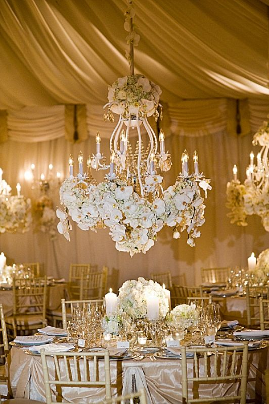 Chandeliers Heavy With White Flowers Hang Above Each Table
