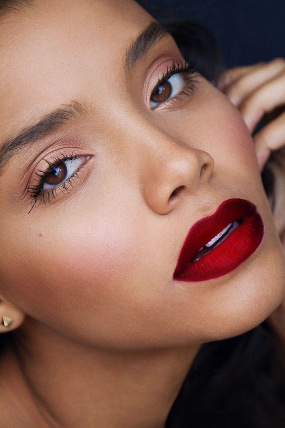 una ragazza con gli occhi color nocciola e le labbra carnose con del rossetto rosso opaco