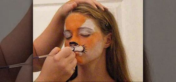 In this video, we learn how to do tiger face paint in two minutes. This is a simple tiger, so it will be perfect for family outings or something you need done quickly. First, use a sponge and orange paint to paint the middle of the face orange. After this, use a sponge with white paint to make the eyes white and the section underneath the nose white. Now, take your orange paint again and paint the cheeks and chin orange. Use the white paint to make fangs on the lips going down to the chin…