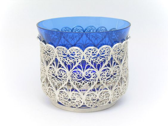 "This Russian elegant filigree basket was made by hand, not by a machine. It is an outstanding example of filigree design and craftsmanship as perfected during the days of Catherine the Great. The pattern is reminiscent of bobbin-lace with seed pearl enhancements.  Hand-crafted in the tiny town of Kazakavo, near Nihzny Novgorod (formerly the city of Gorky). 99.9% pure silver plated. Basket is lacquer protected against tarnish. Includes a heavy cobalt blue glass insert. 4""high, 5"" diameter. A…"