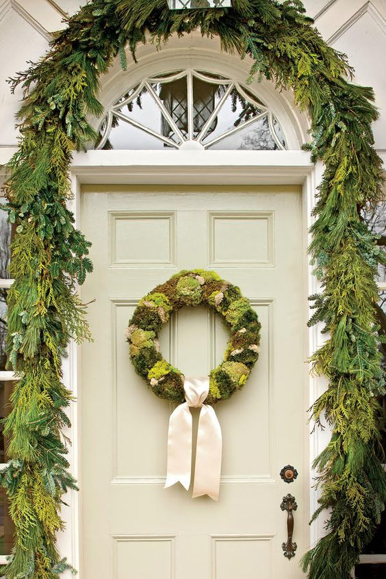 Gorgeous front door decorated for Christmas with evergreen garland and wreath with white ribbon