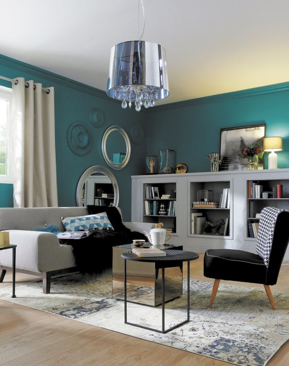 Mur bleu   Sol parquet bois clair   Rideau crème   Canapé noir