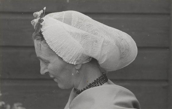 Vrouw in Scheveningse streekdracht. De vrouw is gekleed in de zondagse dracht anno 1953. Ze is 'in het gekleurd' (niet in de rouw). Ze draagt een 'blonde' (kanten) muts, met 'ronde klappen' (zijkanten). Onder de muts een zilveren oorijzer met ovale gouden 'boeken' aan de uiteinden. Achter de boeken zijn twee gouden steekspelden met parel in de muts gestoken. Verder draagt ze gouden oorbellen met een diamant en een granaten halssnoer met gouden slot. #ZuidHolland #Scheveningen