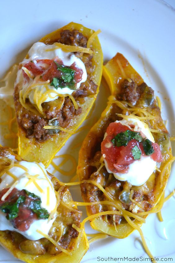 Taco Stuffed Summer Squash Boats | Fresh yellow squash halves stuffed with cheesy taco-seasoned beef, topped with sour cream, tomatoes and fresh cilantro. YUM!