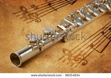 Silver flute on an ancient musical background - stock photo