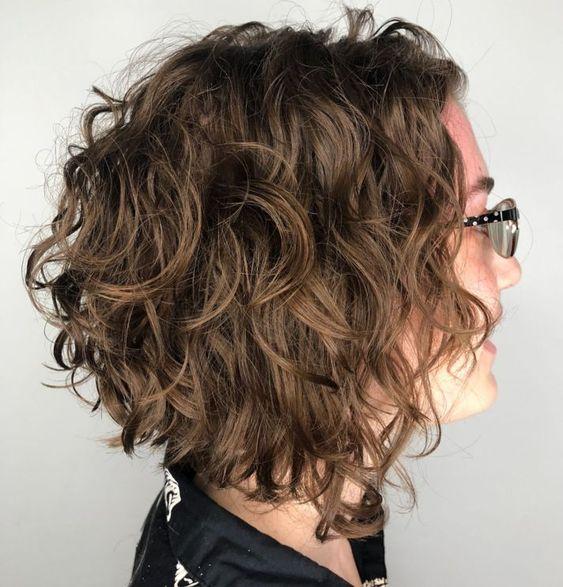 Mujer con corte asimétrico, más corto atrás y cabello ondulado