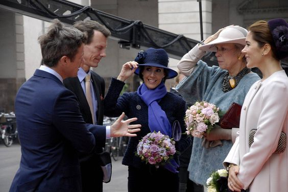 Princess Marie and Princess Benedikte trying desperately not to loose their hats while chatting with Crown Princess Mary, Crown Prince Frederik and Prince Joachim outside the Danish Parliament, on Tuesday.