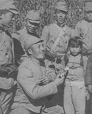 Japanese soldier giving candy to a Chinese girl, 1937-1945.: