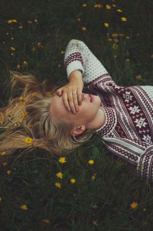 covering eyes while lying in a field.