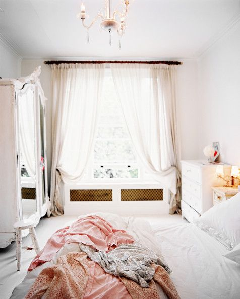 An all-white bedroom feels light and breezy with gauzy drapes and a mirrored armoire.