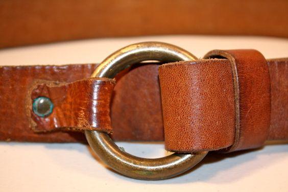 Correa de cuero gruesa de impresionante con hebilla del anillo en bronce. Extremo de la correa recorre y se mantiene muy bien. La pieza al final se cose para que el lado liso del cuero de la muestra a través después de que ha sido colocado a través de. Mide 38 1/2 longitud total (no medida de cintura), 1 1/2 de ancho y 1/4 de espesor.