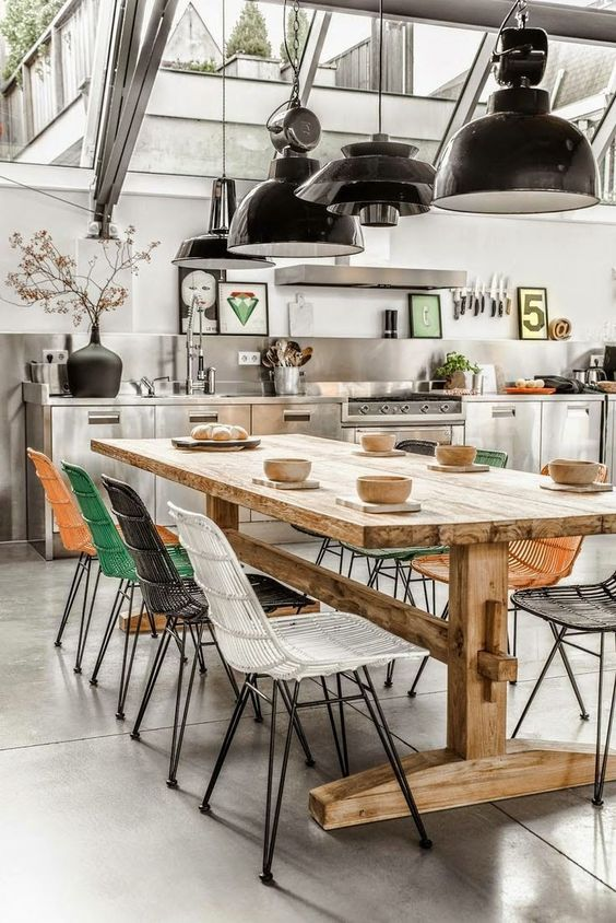 Love everything about this space - utterly cool industrial modern kitchen dining room with black industrial lights, concrete floors and stainless steel kitchen cabinets