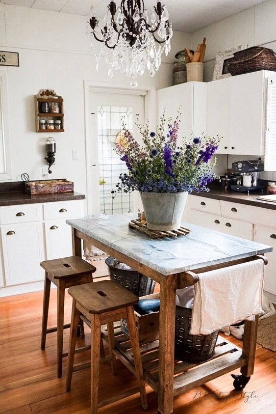 Love this farmhouse kitchen with white cabinets and wood and stainless steel island kellyelko.com #farmhousekitchen #farmhousedecor #farmhouse #kitchen #kitchenisland