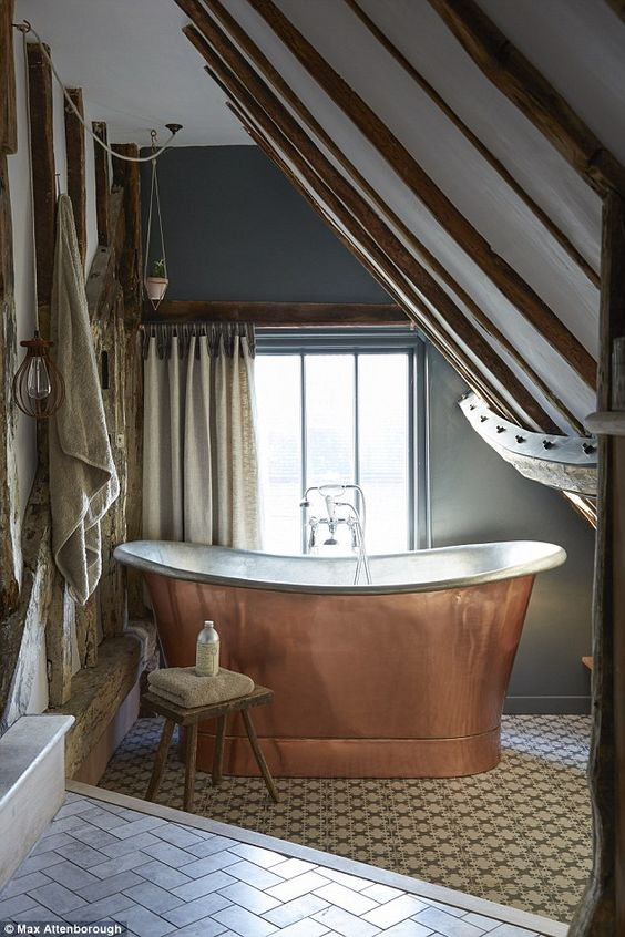 The ensuite bathroom is positioned in the eaves above the kitchen and features original wooden beams. found the copper bath on Ebay for a fraction of what it should cost. The wall is painted in Farrow & Ball's Down Pipe and the tiles are a mix of marble from Fired Earth, laid in a herringbone pattern, and patterned from Surface Tiles