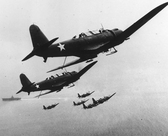 US Navy Dive Bombers above their carrier somewhere in the Pacific