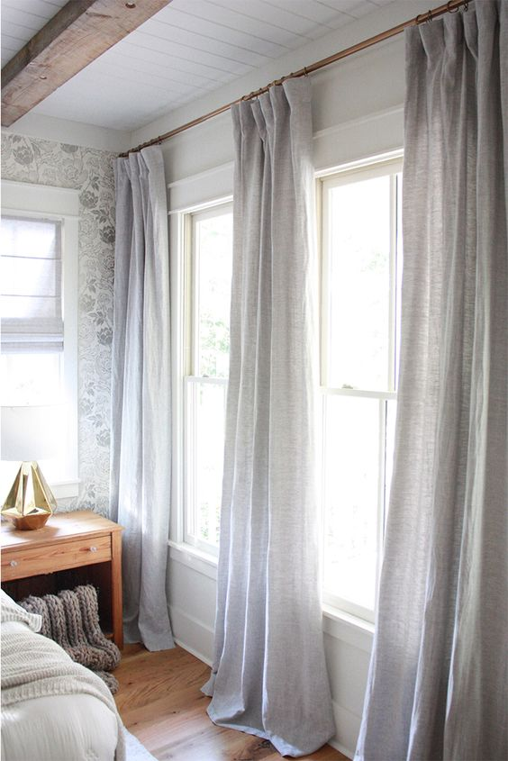 This bedroom takes modern farmhouse a step back to traditional farmhouse details with soft grays and hues of white. The three drapery panels rather than two are the perfect way to bring a little sophistication into the room.