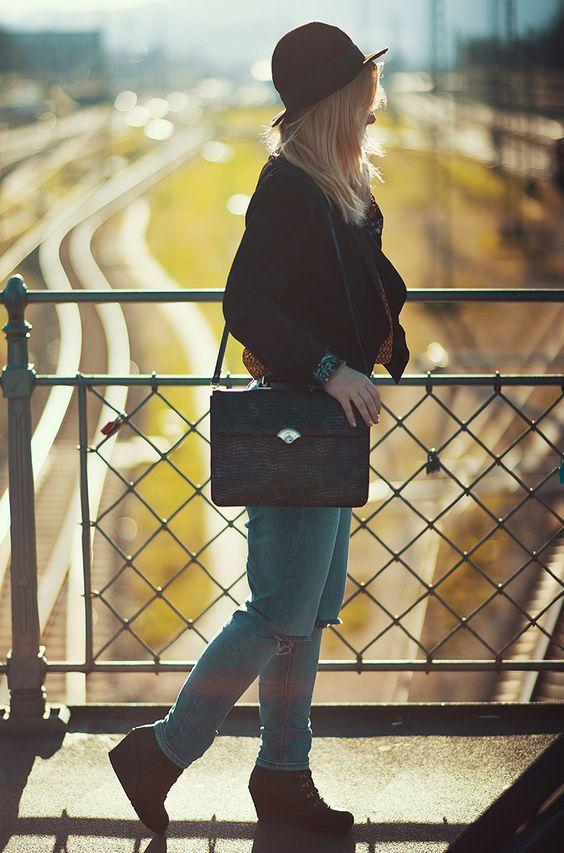 Christina Key trägt einen schwarzen Hut, eine Boyfriend Jeans und eine schicke, schwarze Tasche auf der blauen Brücke in Freiburg