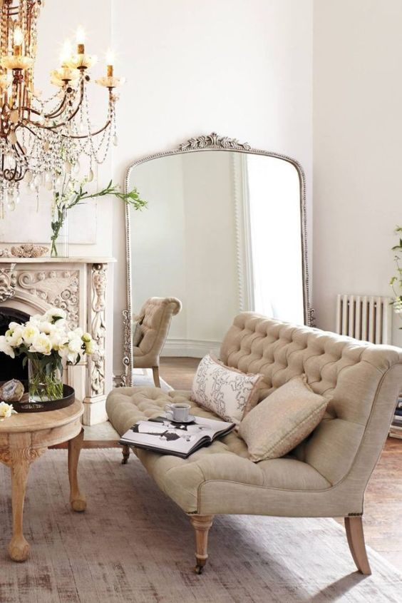 Tufted sofa and French antique fireplace in a Parisian living room. Beautiful Classically Refined Rooms