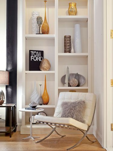 Less is More: Several books stand upright along with tall vases that fill the space without overcrowding it. She also added objects of various height and color to give the bookcase personality.