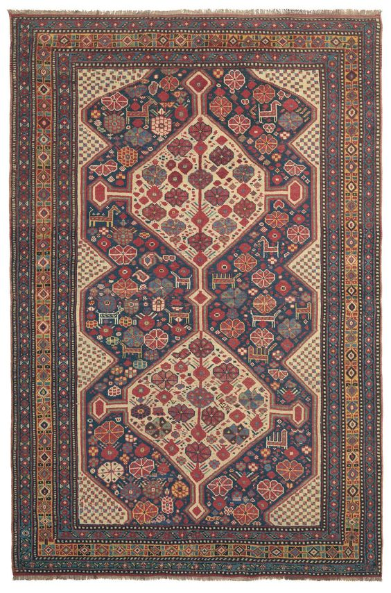 QASHQAI, Southwest Persian, 4ft 3in x 6ft 6in, 3rd Quarter, 19th Century. Of great interest to connoisseurs of tribal Oriental rugs, this nearly 150-year-old South Persian Qashqai tribal is replete with the whimsical charm of its nomadic origins. A multiplicity of freely drawn traditional motifs, including bright blossoms and charming animal designs, fill a deep indigo reserve with two organically drawn hexagonal medallions.