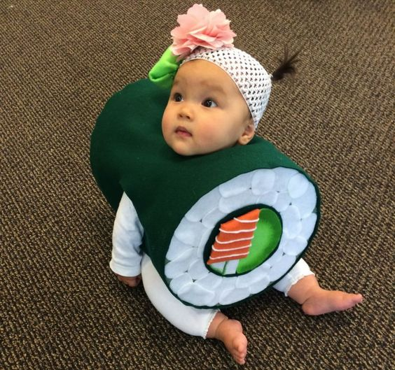 """SUSHI (2014): You know that moment when you first watched """"The Godfather, Part II,"""" and it was so good that it pretty much ruined every mafia-related movie and TV show that followed? This is like that, but with a baby sushi costume. We receive three or four small-child-in-sushi photos every year, but this one is memorable for the details. Note the perfect ratio of salmon-to-cucumber. Note the ginger/wasabi headband. Note how the costume actually helps the baby to sit up. Thanks to Amy…"""