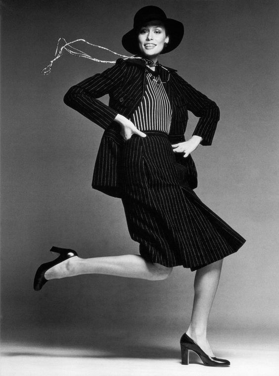 Lauren Hutton is the model most often associated with the 1970s ideal of natural, rangy, athletic, and active beauty. Here she is shown wearing a Galanos pinstripe suit that embodied the working woman's uniform at its most elegant. It was accessorized by de rigueur gold chains, straight-heeled pumps, and a slouchy hat worn low over the brow. —Caroline Rennolds Milbank, 1989 Photo by Francesco Scavullo.