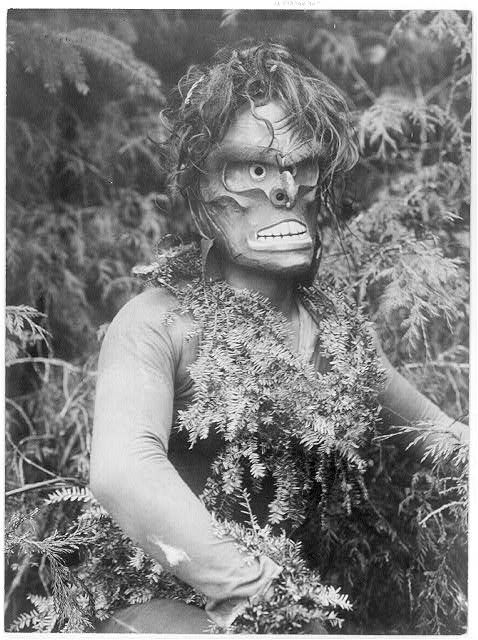 "Title: Paqusilahl–Qagyuhl Date Created/Published: c1914 November 13. Summary: Dancer representing Paqusilahl (""man of the ground embodiment""), wearing a mask and shirt covered with hemlock boughs, representing paqus, a wild man of the woods."