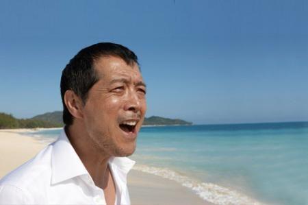 白いシャツを着てビーチで歌っている矢沢永吉の画像