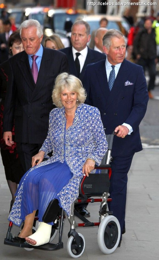 Prince Charles pushes his wife, Camilla Parker Bowles, in a wheelchair into the Royal Opera House. Camilla suffered a broken leg while vacationing in Scotland.