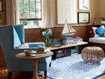 Light wicker furniture and a soft blue wing chair balance a heavier wood.