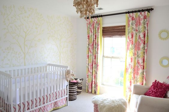 Beautiful stenciled accent wall in this nursery and bright, colorful curtains!