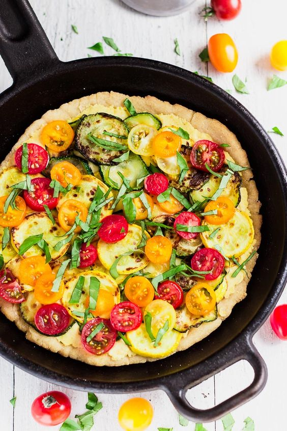 This hummus skillet pizza is the perfect size for two big eaters. The thick and chewy homemade gluten-free pizza crust is topped with veggie and hummus.:
