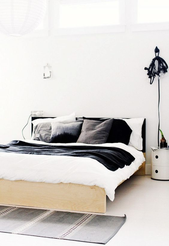 A black and white bedroom with simple bedding and a DIY headboard