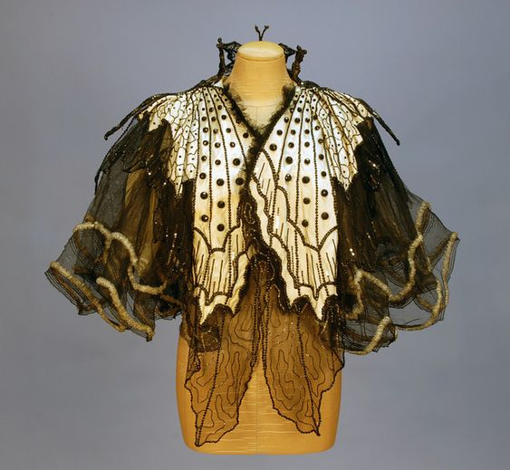 """Sequined and beaded cream satin and black net """"Butterfly"""" evening cape (front) by Emile Pingat, French, 1890s. Satin with chiffon shoulder drape beneath two layers of stiffened black net decorated as butterfly wings with silver sequins and faceted jet beads, the high neck having a large beaded wire butterfly at back. Label """"Maison Emile Pingat A. Walles & Cie 30. Rue Louis le Grand Paris""""."""