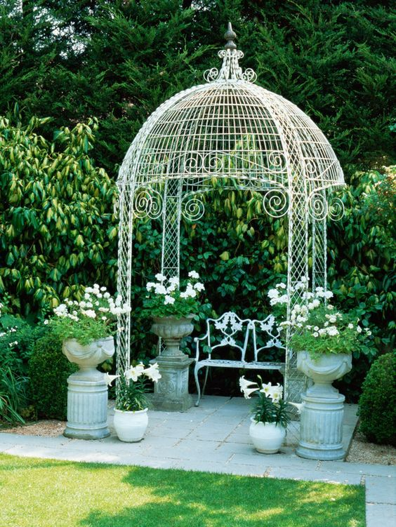 Potted plants help frame this white wire work gazebo.