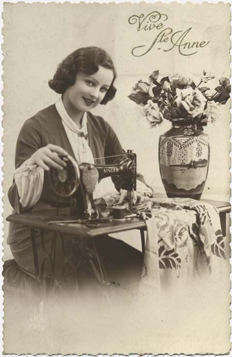 Vintage sewing postcard - lovely lady posing with Singer sewing machine.